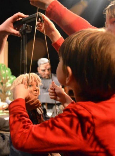 Un niño jugando con unos títeres.