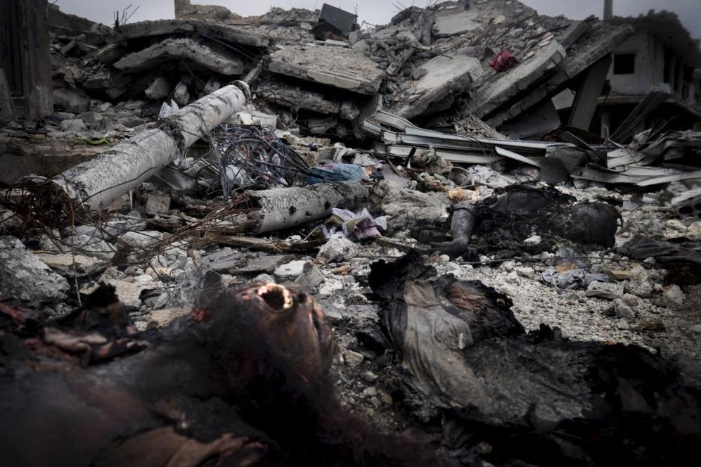 Los cuerpos de varios yihadistas yacen quemados entre las ruinas de...