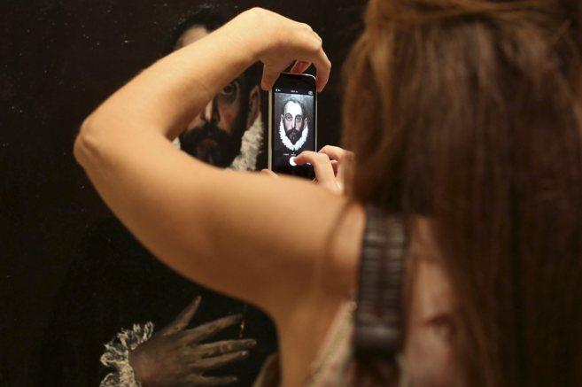 Una mujer toma una fotografía con su móvil del lienzo 'El...