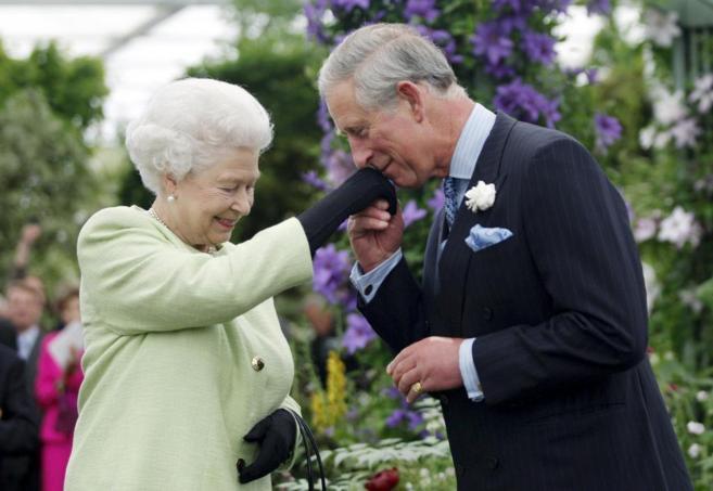 El príncipe Carlos besa la mano de la reina Isabel, durante un acto...