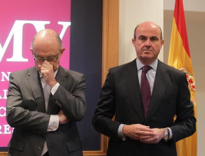 Cristóbal Montoro, ministro de Hacienda, junto a Luis de Guindos,...