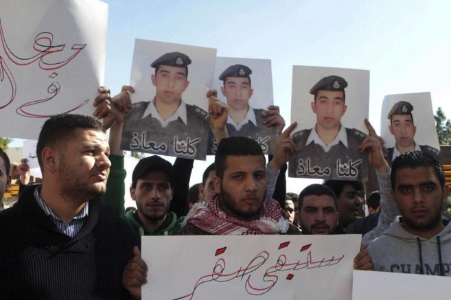 Varios estudiantes muestran fotografías del piloto Muaz Kasasbeh, en...