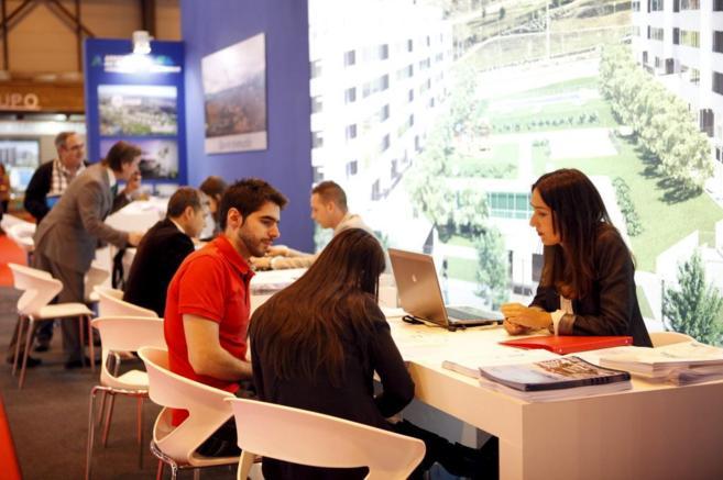 Varios visitantes se informan de la oferta inmobiliaria de uno de los...