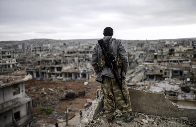 Un miliciano kurdo observa la ciudad destruida de Halimce, al este de...