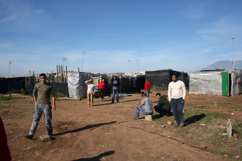 Un grupo de inmigrantes deambula por un asentamiento chabolista de las...