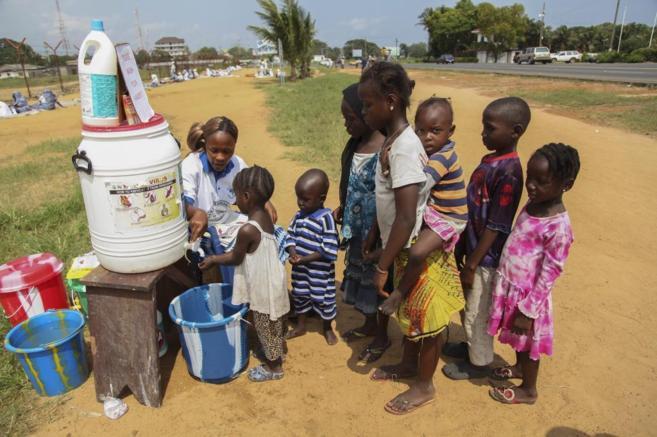 Niños liberianos se lavan las manos para evitar el contagio por...