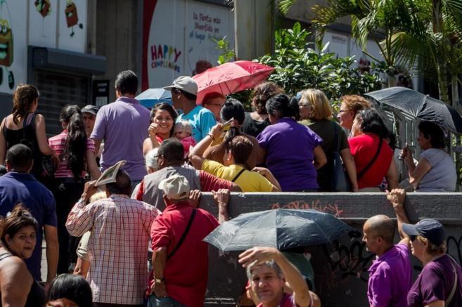 Ciudadanos esperan en una fila para entrar en un establecimiento de...