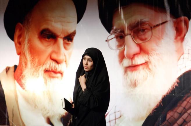 Una mujer iraní camina junto a un cartel con la imagen del ayatolá...