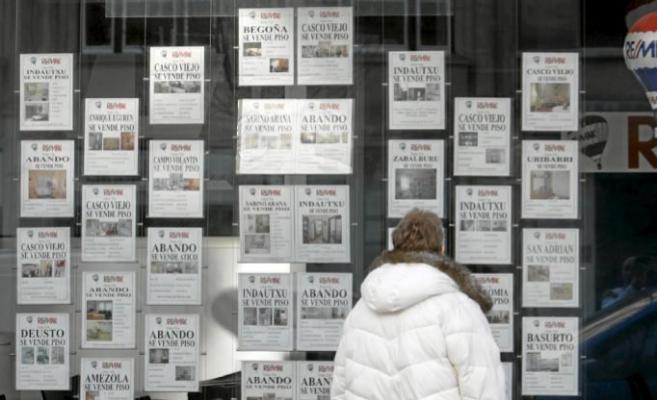 Imagen de archivo de un joven mirando anuncios en el escaparate de una...