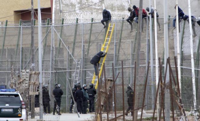 Inmigrantes encaramados en la valla de Melilla.