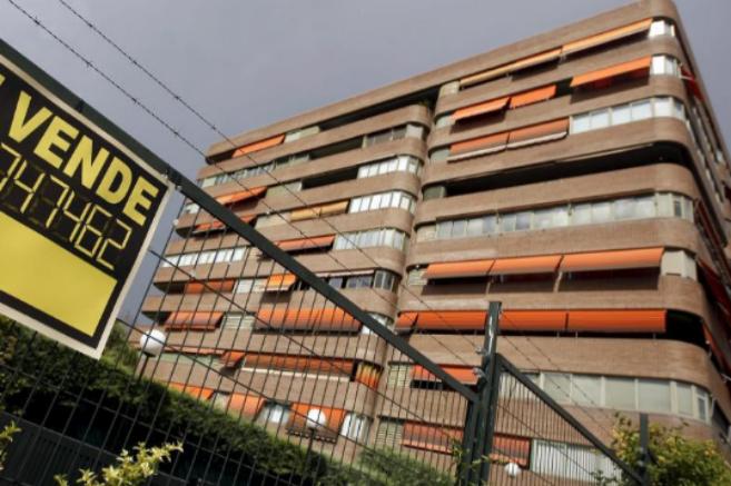 Un cartel de 'Se vende' colgado en la valla de una...