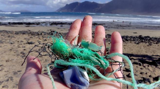 La autora del trabajo, Jenna Jambeck, sostiene muestras de plástico...
