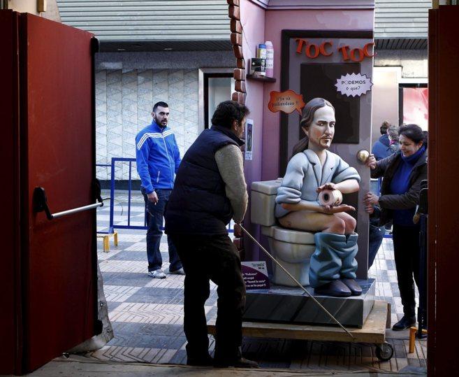 Dos operarios trasladan un 'ninot' de Pablo Iglesias a la...
