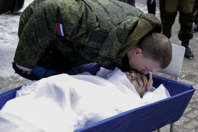 Un miembro de las milicias rebeldes prorrusas participa en el funeral...