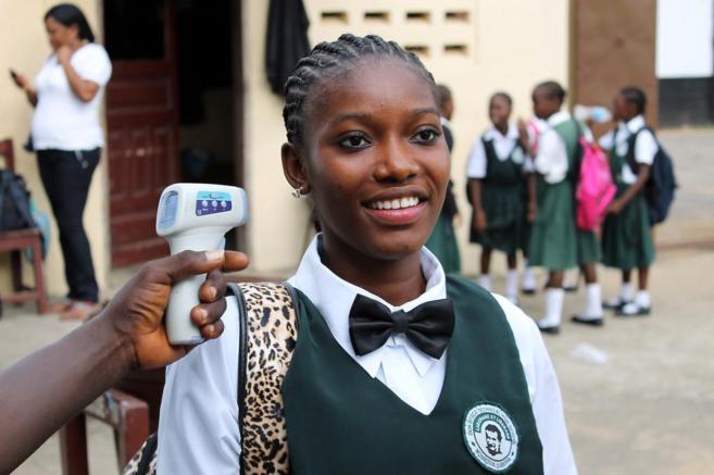 Una estudiante mide su temperatura antes de entrar en clase en el...