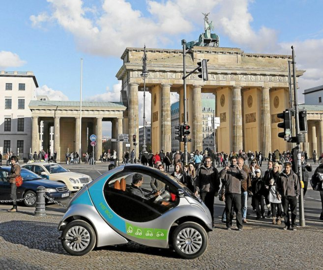Un hombre conduce un modelo de Hiriko en las calles de Berlín, en una...