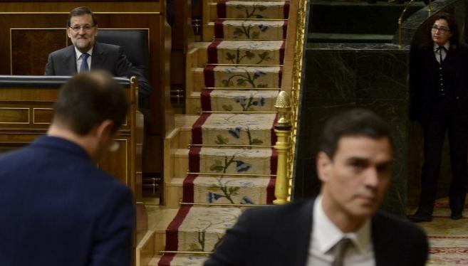 Mariano Rajoy, en su escaño, observa a César Luena (de espaldas) y a...
