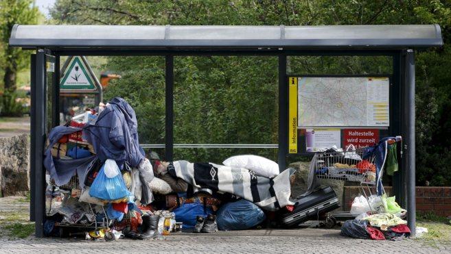 Un mendigo duerme con sus pertenencias bajo la marquesina de un...