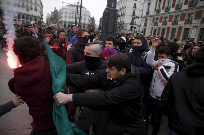 Un joven que porta una bengala se enfrenta con otros manifestantes,...