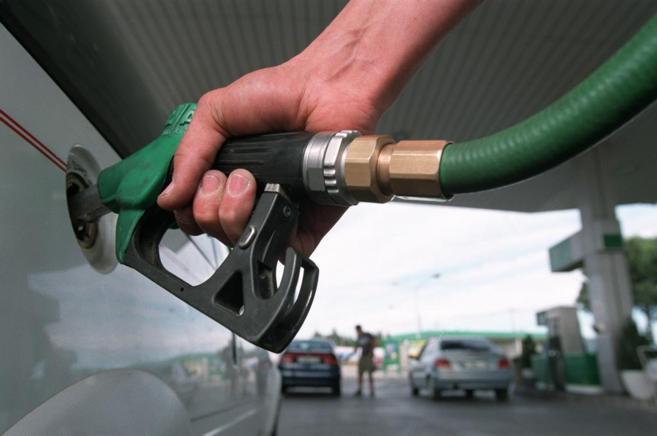Una persona echando gasolina en una estación de servicio