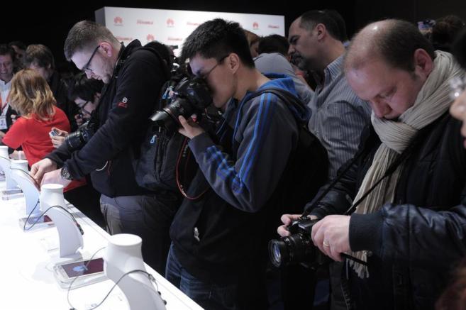 Visitantes fotografían los nuevos modelos de teléfonos expuestos en...