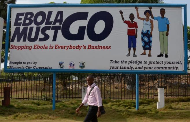 Un hombre camina en Monrovia frente a un cartel con recomendaciones...