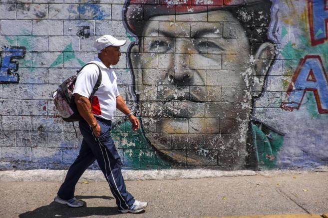 Un hombre camina por delante de un muro con una enorme pintura de...