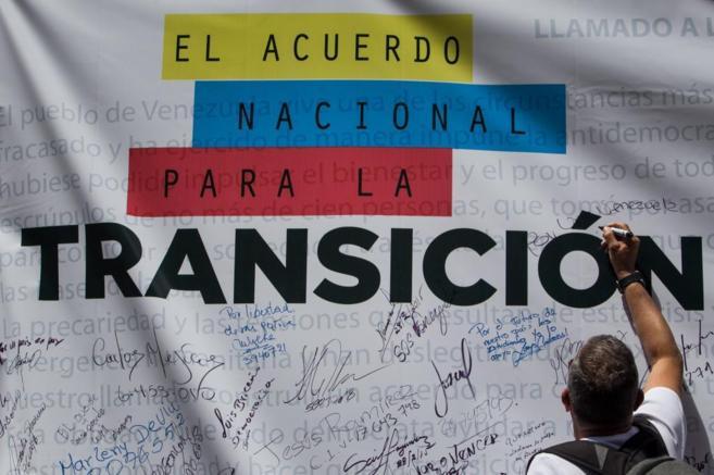 Un ciudadano firma una pancarta de la oposición en favor de una...
