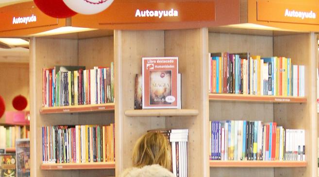 Una mujer consulta la sección de autoayuda en una librería.