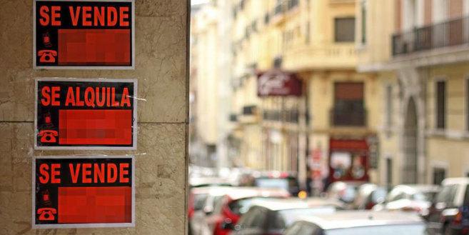 Carteles de venta y alquiler en la entrada a un edificio de viviendas...