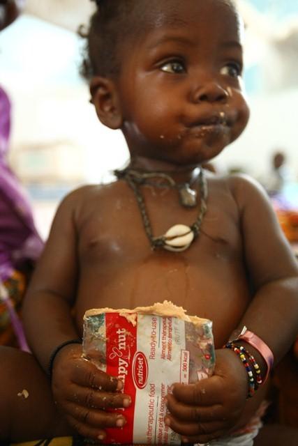 Un niño comiendo un sobre de alimento terapéutico en Sierra Leona
