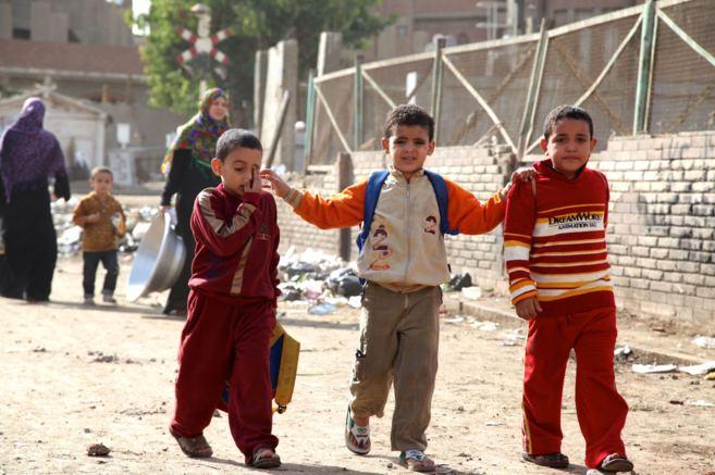 Tres niños caminan por las calles de El Cairo camino de la escuela.