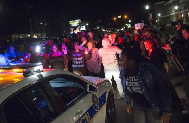 Manifestantes ante un coche de policía, la pasada noche en Ferguson.