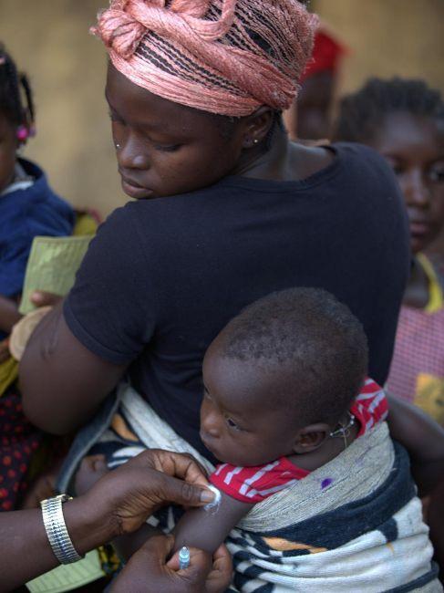 Una mujer sostiene a su hijo mientras lo vacunan contra el sarampión