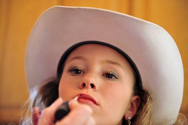 Una niña mientras le pintan los labios.