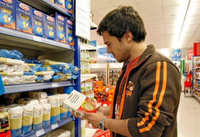Consumidor ante el lineal de pastas de un supermercado con marcas de...