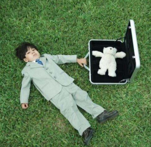 Un niño vestido de traje gris con un maletín en el que guarda un oso...