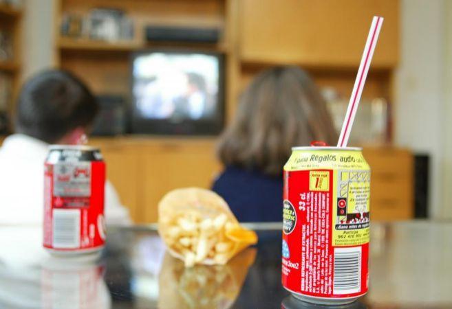 Dos niños toman refrescos y patatas fritas mientras ven la...