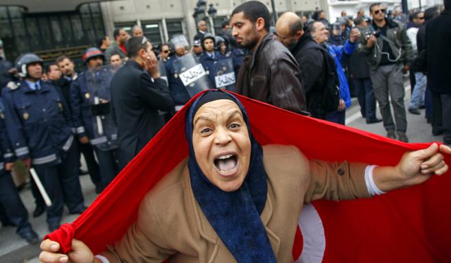 Una manifestante cubierta por una bandera tunecina corea consignas...