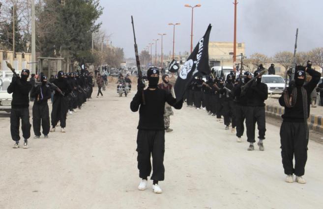 Yihadistas del IS desfilan armados en la localidad siria de Tel Abyad.