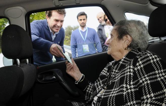 Una anciana de 98 años entrega el voto al presidente de la mesaen...