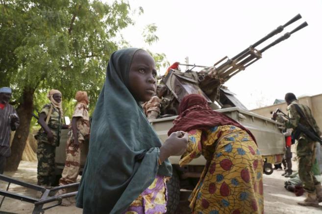 Una niña parada frente a soldados de Níger y Chad en la ciudad...