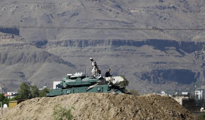 Rebeldes hutíes permanecen sentados en un tanque cerca del Palacio...