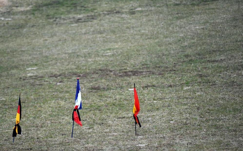 Las banderas de Alemania, Francia y España atadas con un crespón...