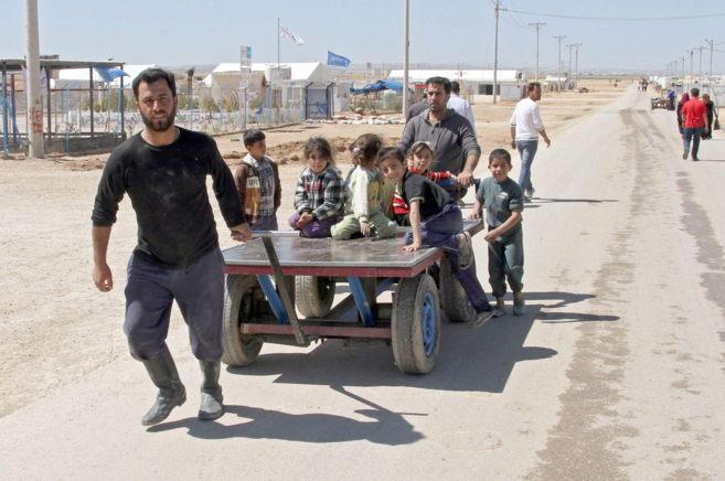 Un refugiado sirio tira de un carro con niños en el campo de...