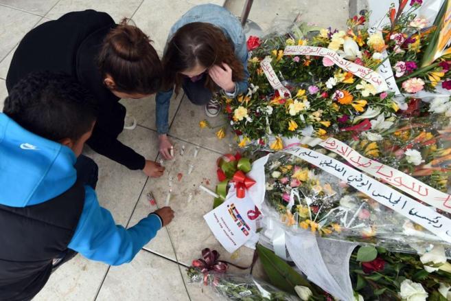 Un grupo de turistas colocan flores por las víctimas en el Museo...
