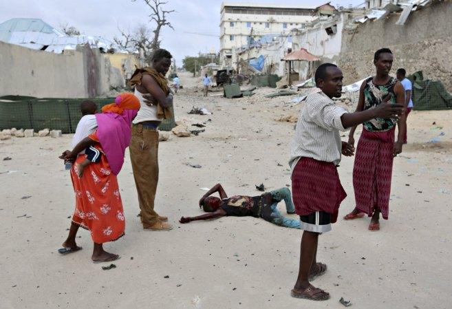 Vecinos de Mogadiscio se preparan para asistir a un niño herido tras...
