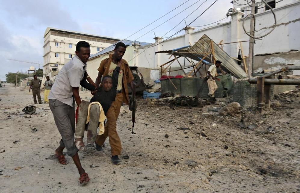 Los residentes evacuan a un muchacho herido tras el ataque producido...