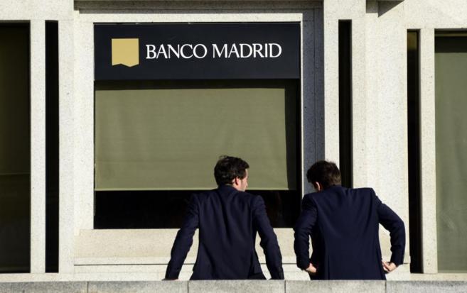Dos empleados de Banco Madrid a las puertas de una oficina de la...