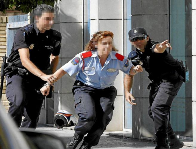 Agentes de la Policía Nacional indican a una vigilante de seguridad...